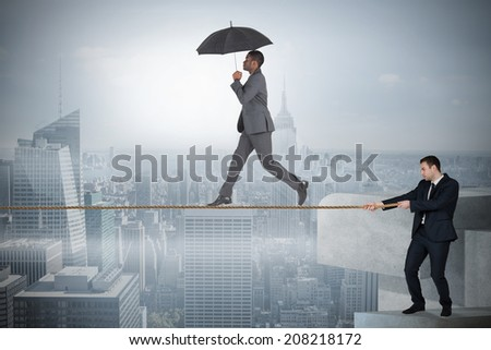 Young business man pulling a tightrope for businessman against misty cityscape - stock photo