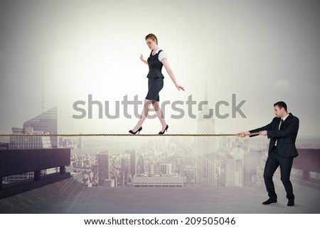 Young business man pulling a tightrope for businesswoman against cityscape on the horizon - stock photo