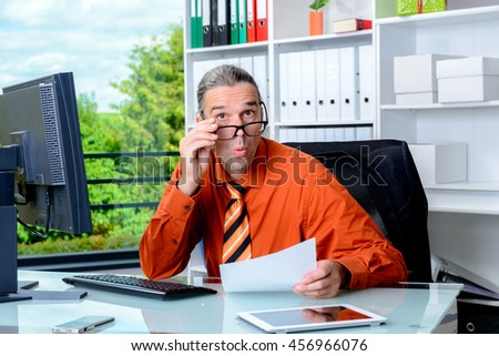 young business man reading letter and is amazed - stock photo