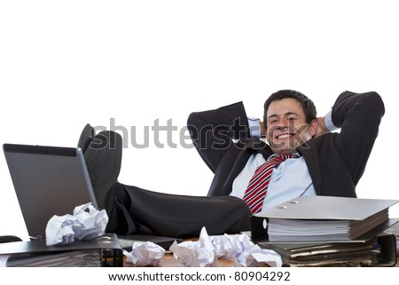 Young business man relaxes with feet at desk. Isolated on white background. - stock photo