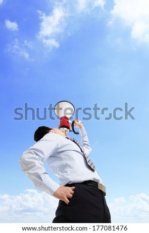 Young business man shouting into a megaphone up forward to sky, copy space - stock photo
