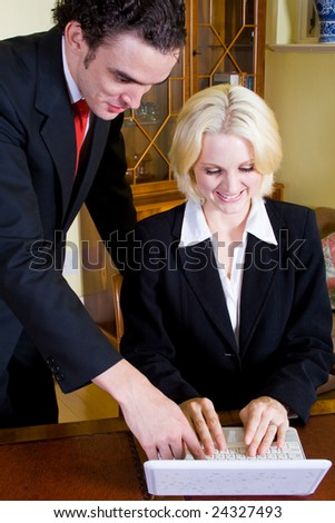 young business man showing showing report to his secretary on a laptop - stock photo