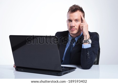 young business man sitting at his laptop and looking pensively into the camera while holding his fingers at his temples. on a gray studio background