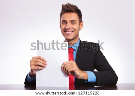 young business man sitting at the desk and holding / presenting a bunch of papers while smiling at the camera - stock photo