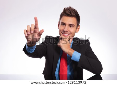 young business man sitting at the table and touching an imaginary button with his finger while pensively looking at it - stock photo