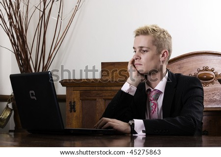 Young business man sitting by a table in front of he's computer/laptop/notebook. - stock photo