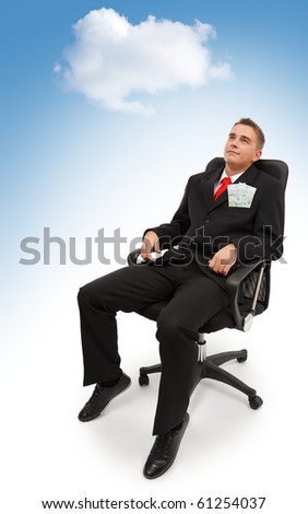 Young business man sitting in chair, under cloudy blue sky and dreaming about spending the money he has
