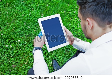 Young business man sitting in city park holding computer tablet