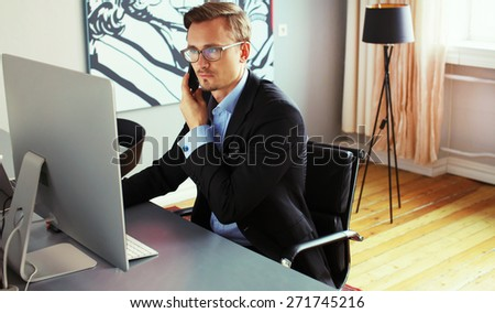 Young business man speaking on the phone in office. - stock photo