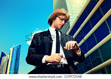 Young business man standing in the big city and looking at his wristwatch.