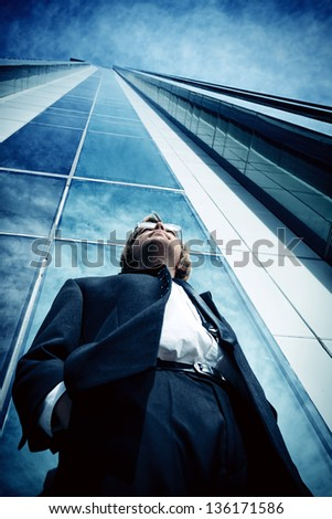 Young business man standing in the big city and purposefully looking away. - stock photo