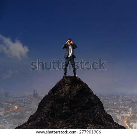 young business man standing on top of mountain and spying by binocular looking for something - stock photo