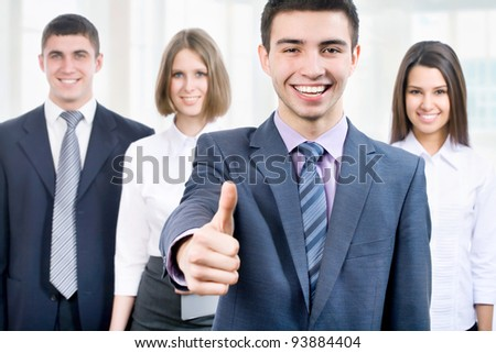 Young business man standing with his staff in background at office