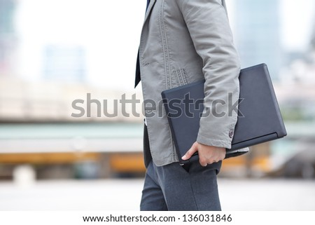 young business man standing with laptop - stock photo