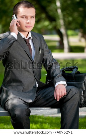 Young business man talking by mobile cell phone, at green park. Student. - stock photo