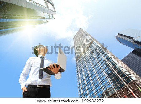 Young business man using laptop and look to blue sky and cloud with cityscape, hong kong, asia, business and cloud computing concept