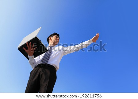 Young business man using laptop and look to blue sky, business concept - stock photo