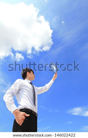 Young business man using tablet pc and look to blue sky and cloud with cityscape in the background, business and cloud computing concept - stock photo