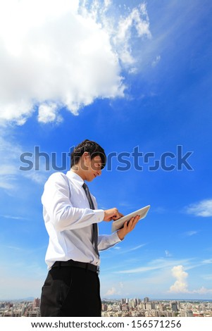 Young business man using tablet pc with cityscape and cloud in the background, business and cloud computing concept - stock photo