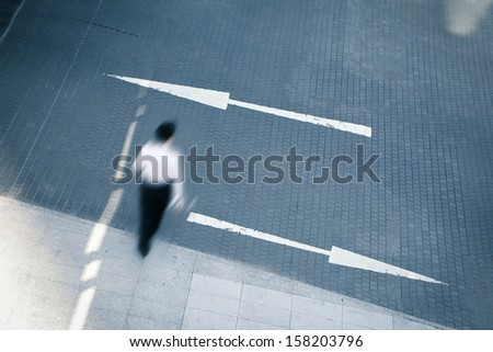 young business man walking with two arrows, business concept - stock photo