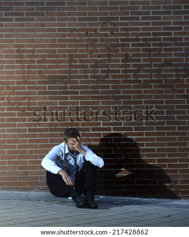 Young business man who lost job abandoned and lost in depression sitting on ground street corner against brick wall suffering emotional pain, crying alone in edgy lighting - stock photo