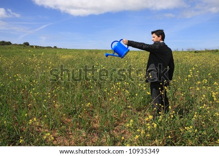 Young business man with a blue watering can in a field - stock photo