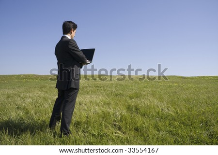 Young business man with a laptop on a green field