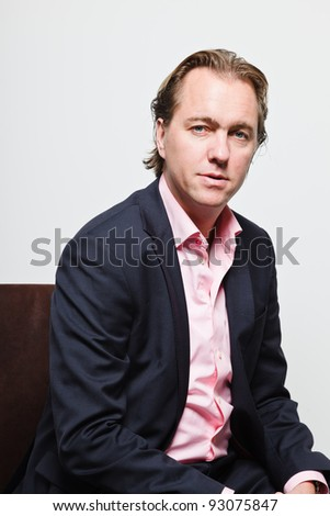 Young business man with blond hair in blue suit and pink shirt serious looking isolated on white background