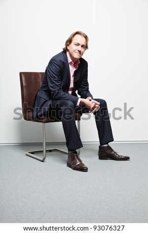 Young business man with blond hair in blue suit and pink shirt sitting on chair in office