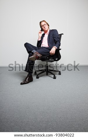 Young business man with blond hair in blue suit and pink shirt sitting on chair in office. Wearing glasses. Calling with cellphone. - stock photo