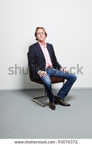 Young business man with blond hair in blue suit and pink shirt wearing glasses sitting on chair in office
