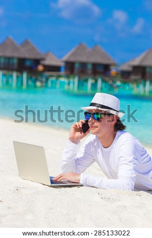 Young business man with computer and cell phone on white beach