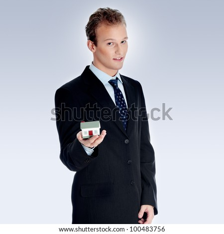 Young business man with house model on hand- real estate concept. - stock photo