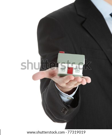 Young business man with house model on hand- real estate concept. Isolated on white - stock photo