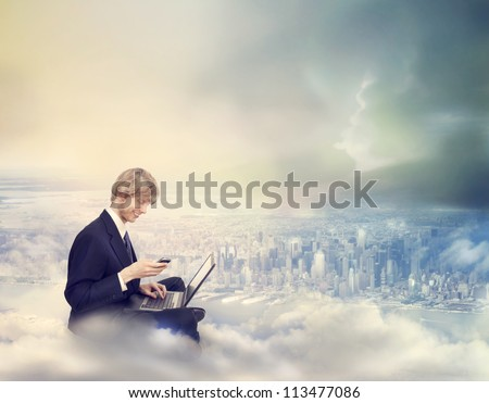 Young Business Man with Laptop and Phone on Top of the City - stock photo