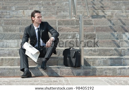 Young business man with newspaper sitting on the stairs.