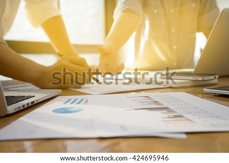 young business man woman executive meeting consulting  startups for make marketing analysis  plan on table. with many computer mobile phone paper graph book and pen in vintage tone.  - stock photo