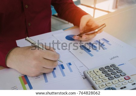 young business man working finance about cost and calculator, strategy diagram chart report and mobile phone on desk at home office, financial, business technology and investment concept