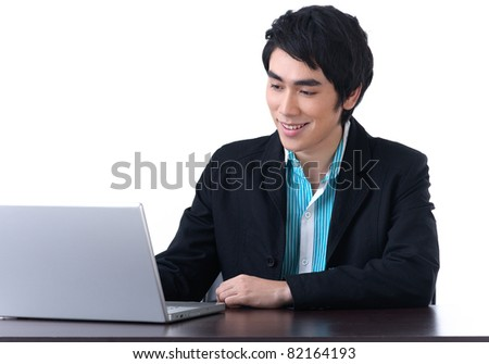 Young business man working happily with laptop - stock photo
