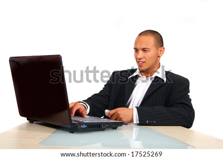 Young Business Man Working On His Laptop A young businessman sitting by desk at office working on the laptop with cellphone on the table. - stock photo