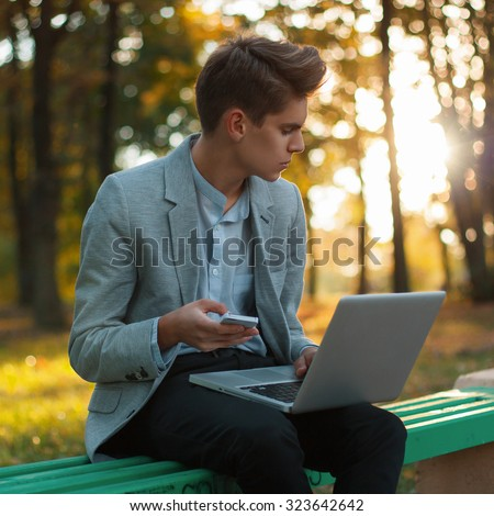 Young business man working with laptop and cellphone, outdoors. Beautiful sunset in the park - stock photo
