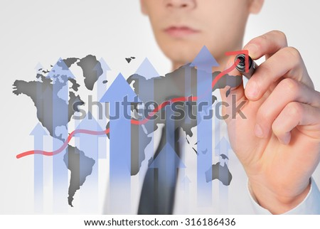 Young business man writing world graph - stock photo