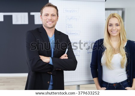 Young business management team about to give a presentation posing together in front of a flip chart smiling at the camera - stock photo