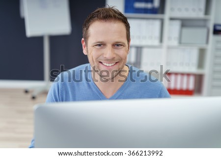 Young business manager at work at his desk in the office sitting behind a desktop monitor smiling over the top at the camera - stock photo