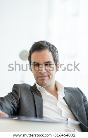 Young business manager sitting at his office desk frowning upon a document or annual report he is reading. - stock photo