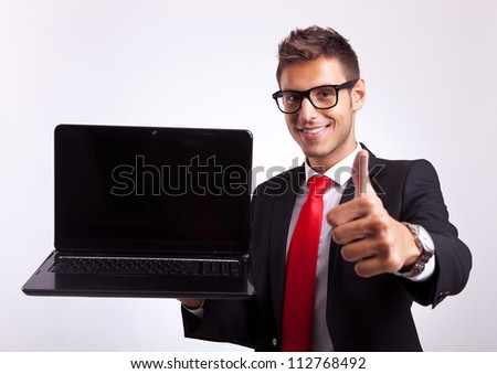 young business manor student giving the ok for the new laptop computer - stock photo