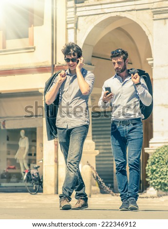 Young business men in the city main square with smartphone having a break after a working day texting sms messages - Modern concept of urban and metropolitan life on a vintage filtered look - stock photo