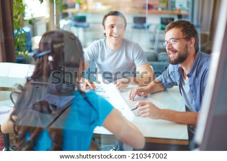 Young business partners discussing ideas or project at meeting in office - stock photo
