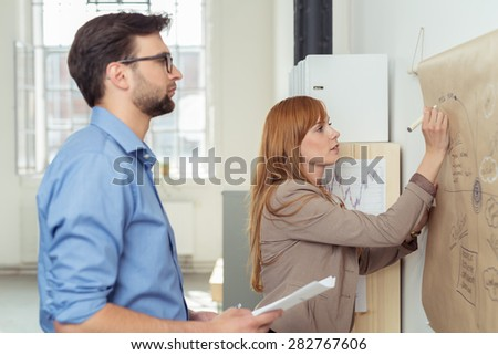 Young Business Partners Making a Project Concept Diagram Using a Poster Paper on the Wall. - stock photo