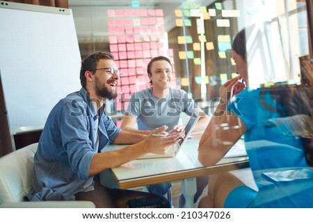 Young business partners sharing ideas and planning work at meeting in office - stock photo